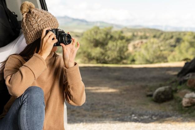 Mujer sentada en el maletero del coche durante un viaje por carretera y sosteniendo la cámara