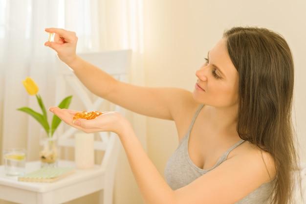 Mujer sentada mañana en la cama toma vitaminas, aceite de pescado omega-3 vitamina e