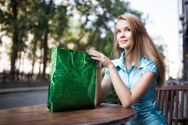 Mujer sentada a la mesa con bolsa de papel en las manos