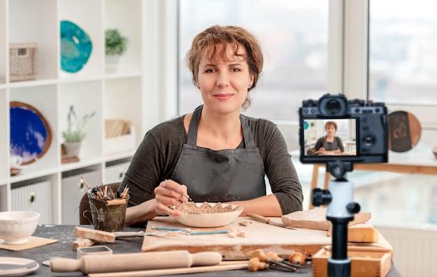 Mujer sentada a la mesa con cerámica durante el trabajo en el taller de luz. profesión de bloguero