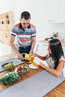 Mujer sentada en la mesa de la cocina comer maíz hablar con el hombre cortando maíz.