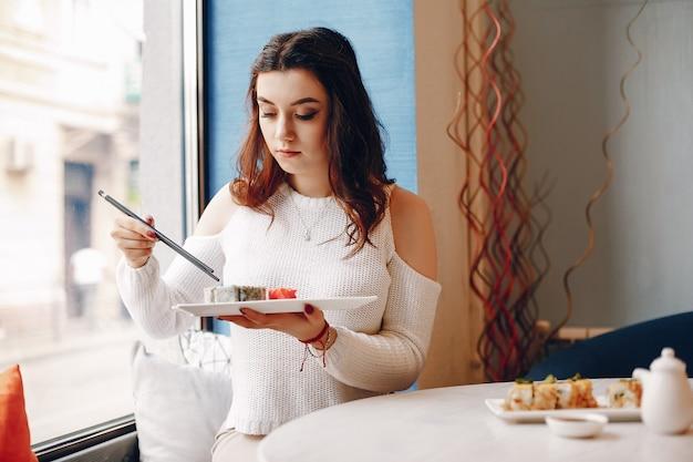 Mujer sentada en la mesa y comiendo sushi en la cafetería