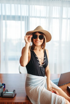 Mujer sentada en la mesa en la oficina y pensando en la aventura de verano.