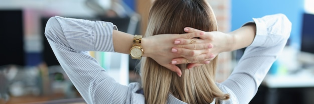 Mujer sentada a la mesa y sosteniendo sus manos detrás de la cabeza concepto de negocio femenino exitoso