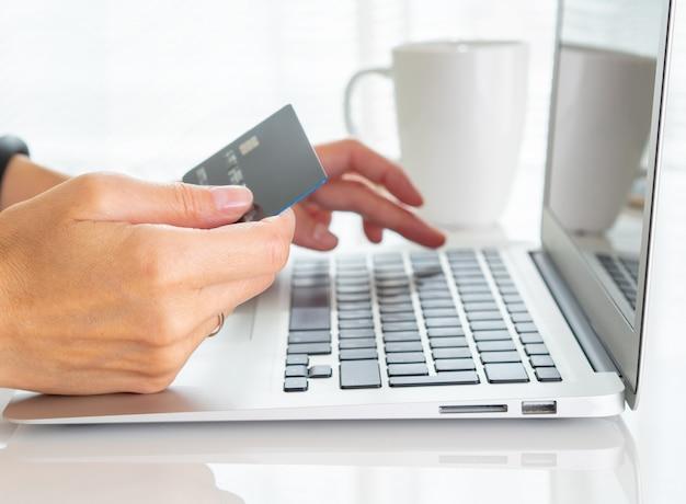 Mujer sentada en una mesa, tomando té y mirando una computadora portátil, pagar las compras