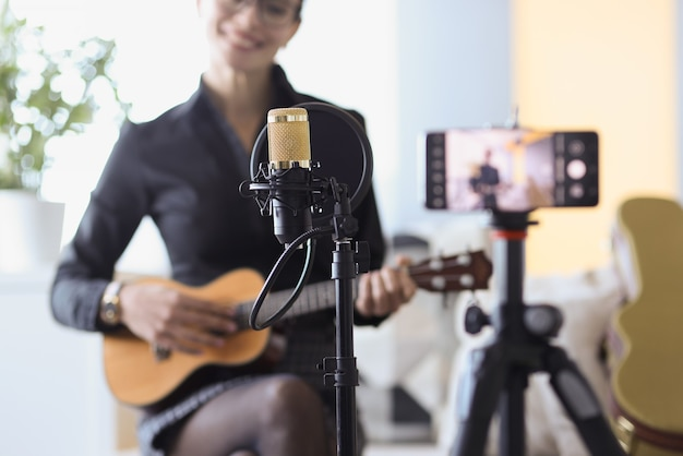 Mujer sentada con micrófono y sosteniendo el ukelele frente a primer plano de la cámara. concepto de blogs independientes