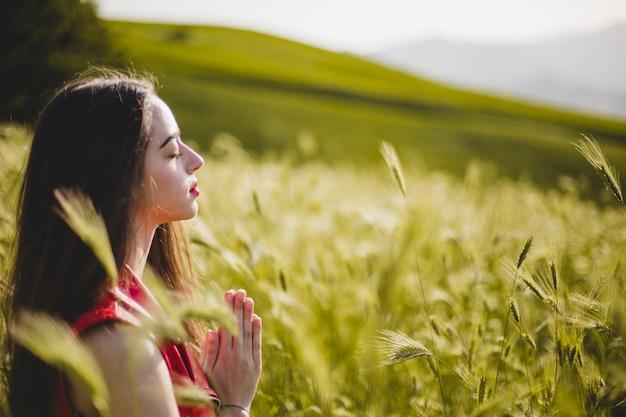 Mujer sentada en la naturaleza y meditando