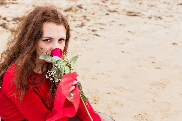 Mujer sentada en la orilla del mar y oliendo rosa