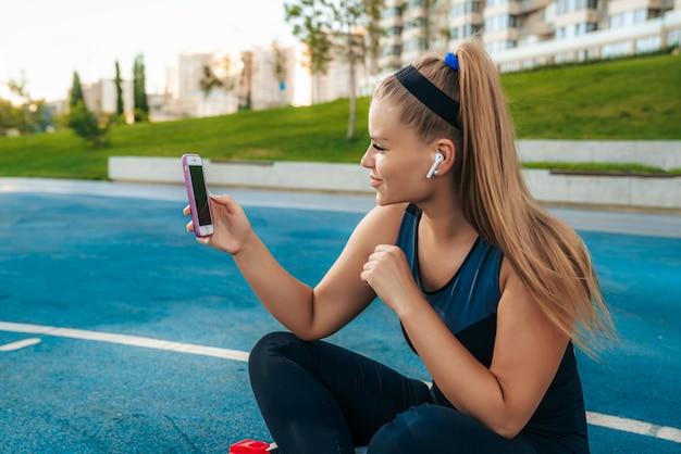 Mujer sentada en el patio de recreo con un teléfono en sus manos