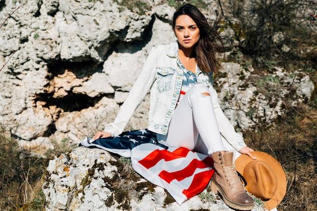 Mujer sentada en piedra con bandera americana