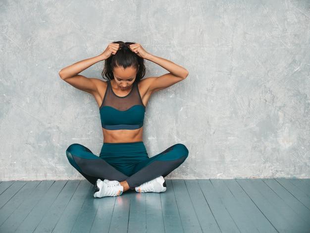 Mujer sentada en el piso en estudio cerca de la pared gris