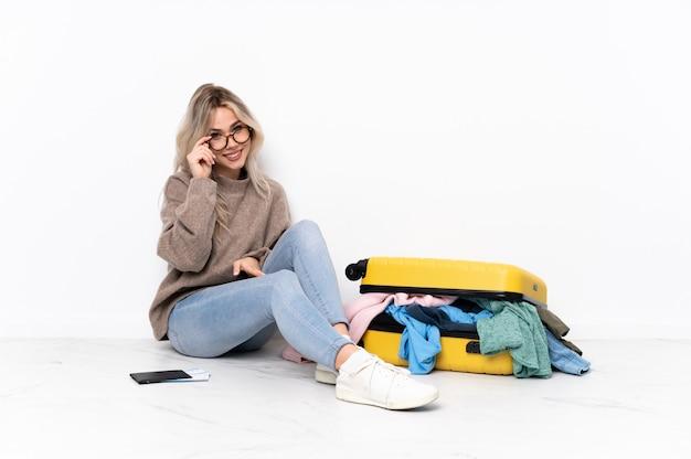 Mujer sentada en el piso con maleta sobre pared aislada