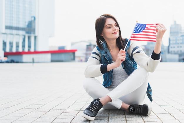 Mujer sentada en la plaza y sosteniendo la bandera estadounidense en la mano