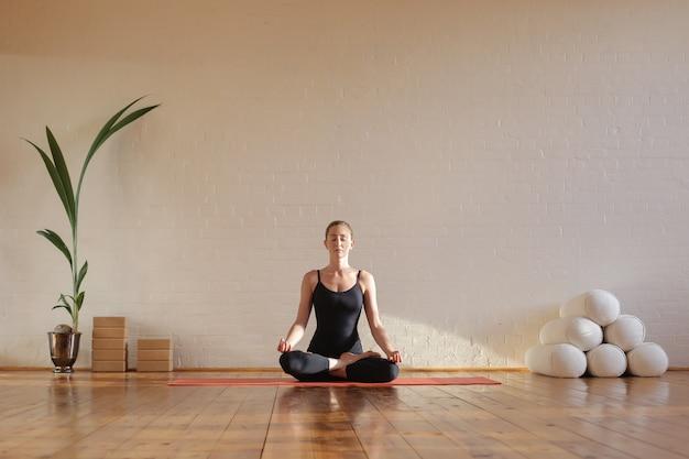 Mujer sentada en posición de loto meditando