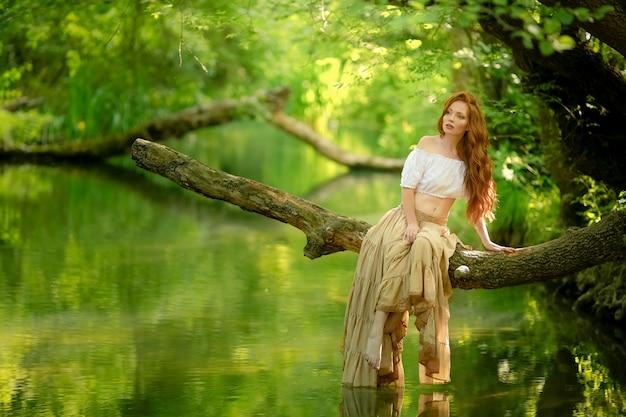 Una mujer sentada en una rama de un árbol bajado sobre el río.