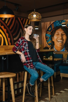 Mujer sentada en silla de bar con café en café