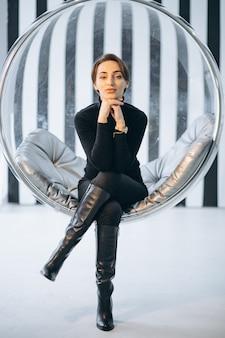 Mujer sentada en silla colgante de cristal