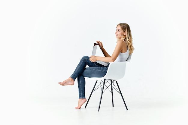 Mujer sentada en una silla con comunicación por internet portátil en línea. foto de alta calidad
