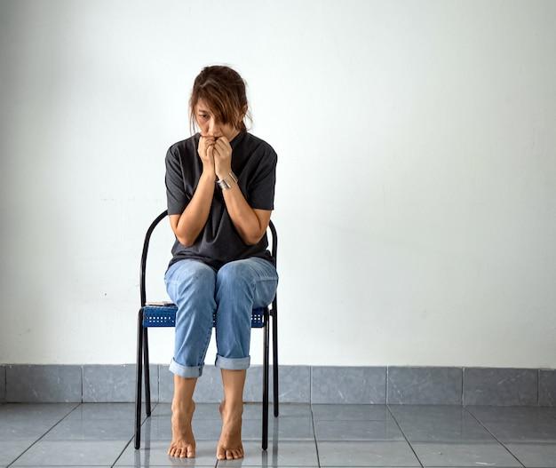 Mujer sentada en una silla, con estrés y malestar. tiene problemas mentales.