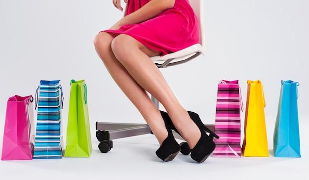 Mujer sentada en una silla junto a bolsas de la compra.