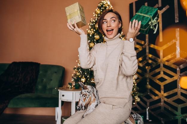 Mujer sentada en una silla pony de madera junto al árbol de navidad