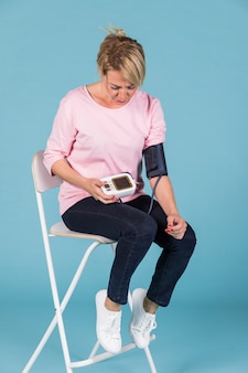Mujer sentada en una silla que controla la presión sanguínea en un tonómetro eléctrico