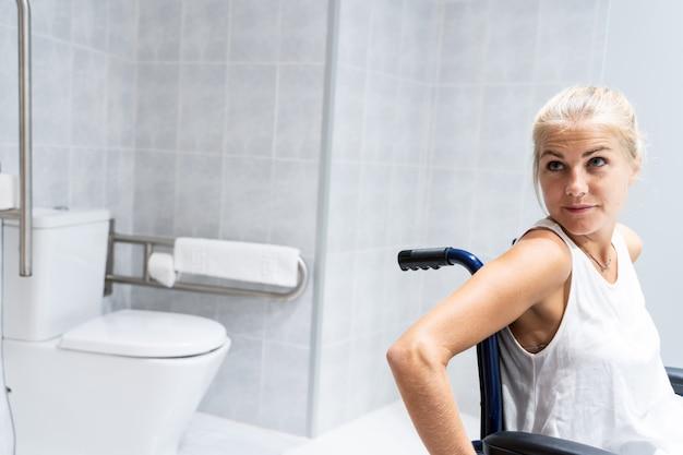 Mujer sentada en una silla de ruedas en un baño con el inodoro detrás