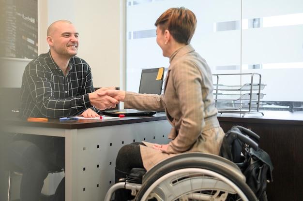 Mujer sentada en silla de ruedas dándose la mano