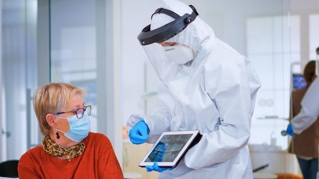 Mujer sentada en una silla en la sala de espera con máscara de protección escuchando médico con aspecto general en tableta en clínica con nueva normalidad. asistente explicando problema dental durante la pandemia de coronavirus
