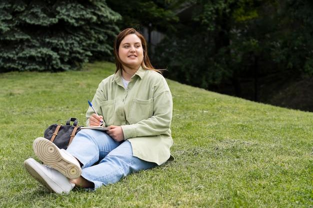 Mujer sentada sobre el césped full shot