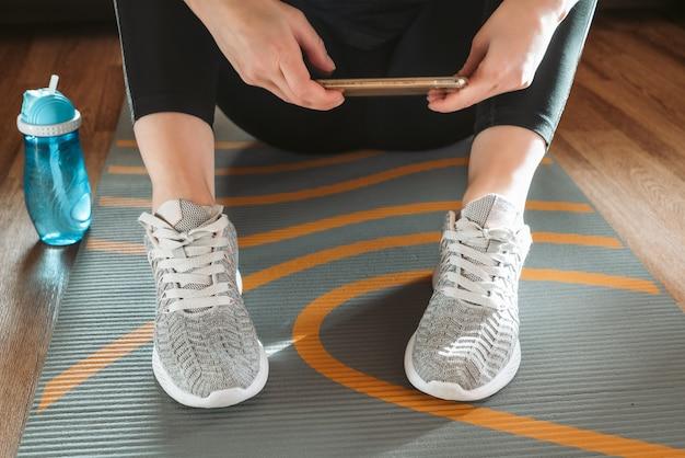 Mujer sentada sobre una estera de yoga enrollada en el suelo viendo ejercicio de yoga en línea en el teléfono inteligente