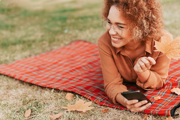 Mujer sentada sobre una manta con espacio de copia
