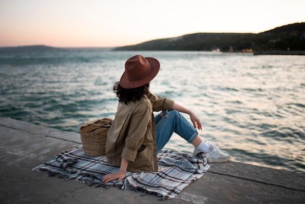 Mujer sentada sobre una manta full shot