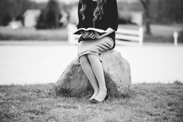 Mujer sentada sobre una roca mientras lee un libro en escala de grises