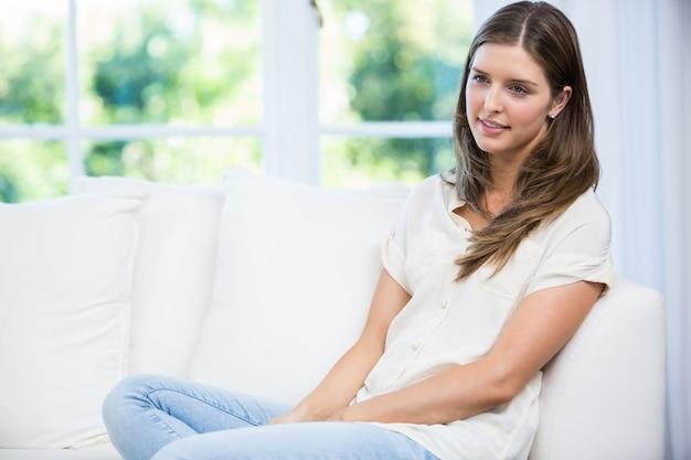 Mujer sentada en el sofá y discutiendo con pareja