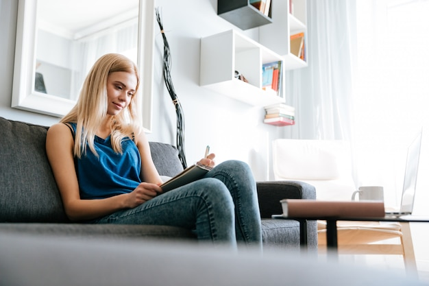 Mujer sentada en el sofá y escribiendo en el bloc de notas en casa