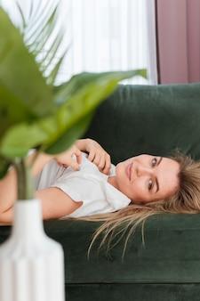 Mujer sentada en el sofá y planta en un florero