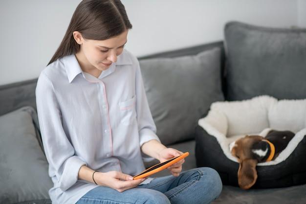 Una mujer sentada en un sofá y trabajando en una computadora portátil