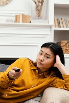 Mujer sentada en el sofá y viendo la televisión
