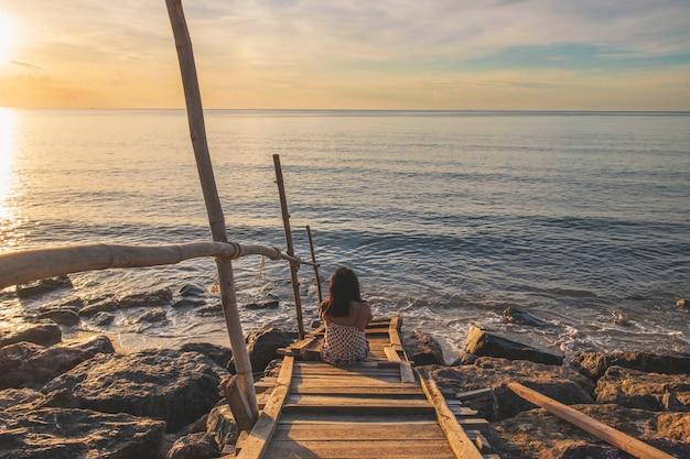 Una mujer sentada sola en la playa en verano.