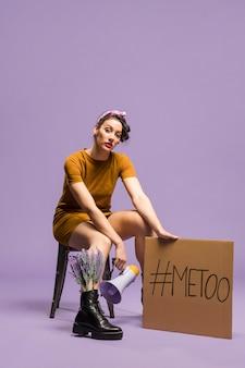 Mujer sentada y sosteniendo cartón
