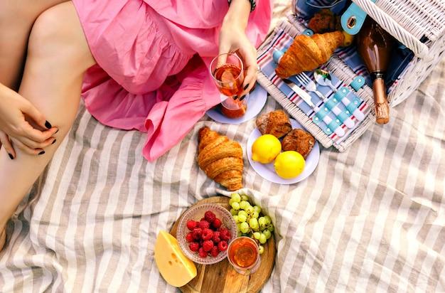 Mujer sentada y sosteniendo una copa de champán, frutas tradicionales, croissants y queso,