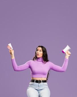 Mujer sentada y sosteniendo tarjetas de crédito y megáfono