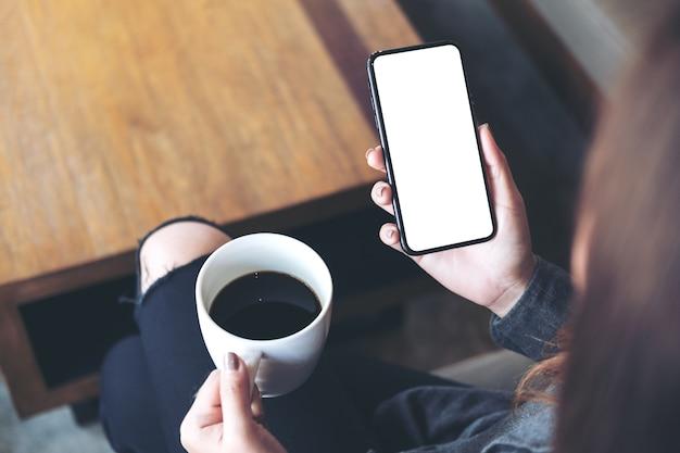Mujer sentada y sosteniendo el teléfono móvil negro con pantalla de escritorio en blanco en el muslo