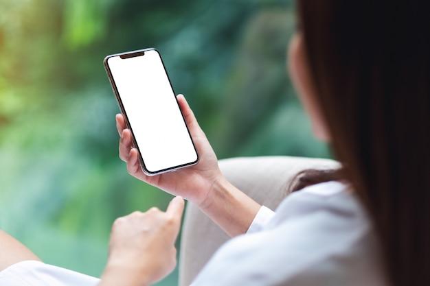 De una mujer sentada y sosteniendo el teléfono móvil con pantalla de escritorio en blanco, naturaleza verde borrosa