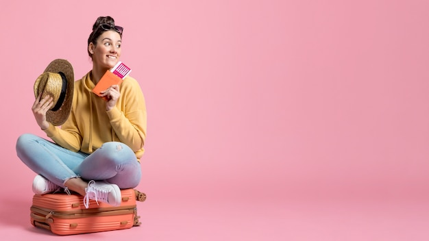 Mujer sentada en su equipaje con espacio de copia