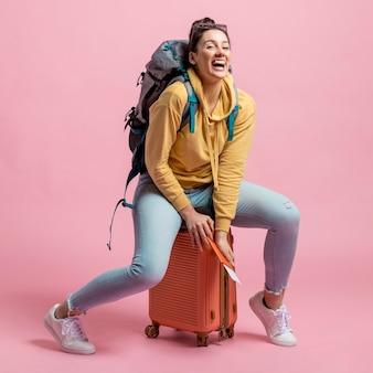 Mujer sentada en su equipaje mientras se reía
