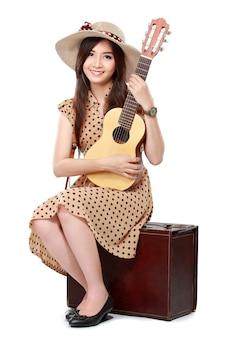 Mujer sentada en su maleta mientras toca la guitarra
