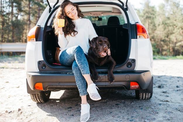 Mujer sentada con su perro en maletero abierto