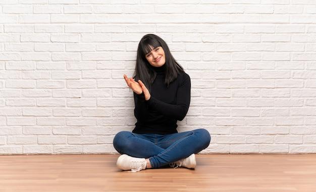 Mujer sentada en el suelo aplaudiendo después de la presentación en una conferencia